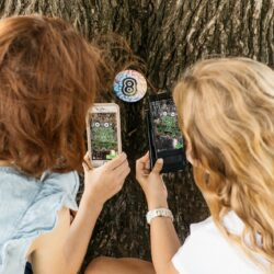 Two little girls are pointing their phones at a disc located at the base of a tree trunk. The disc activates a video of a creature on their phone's screen