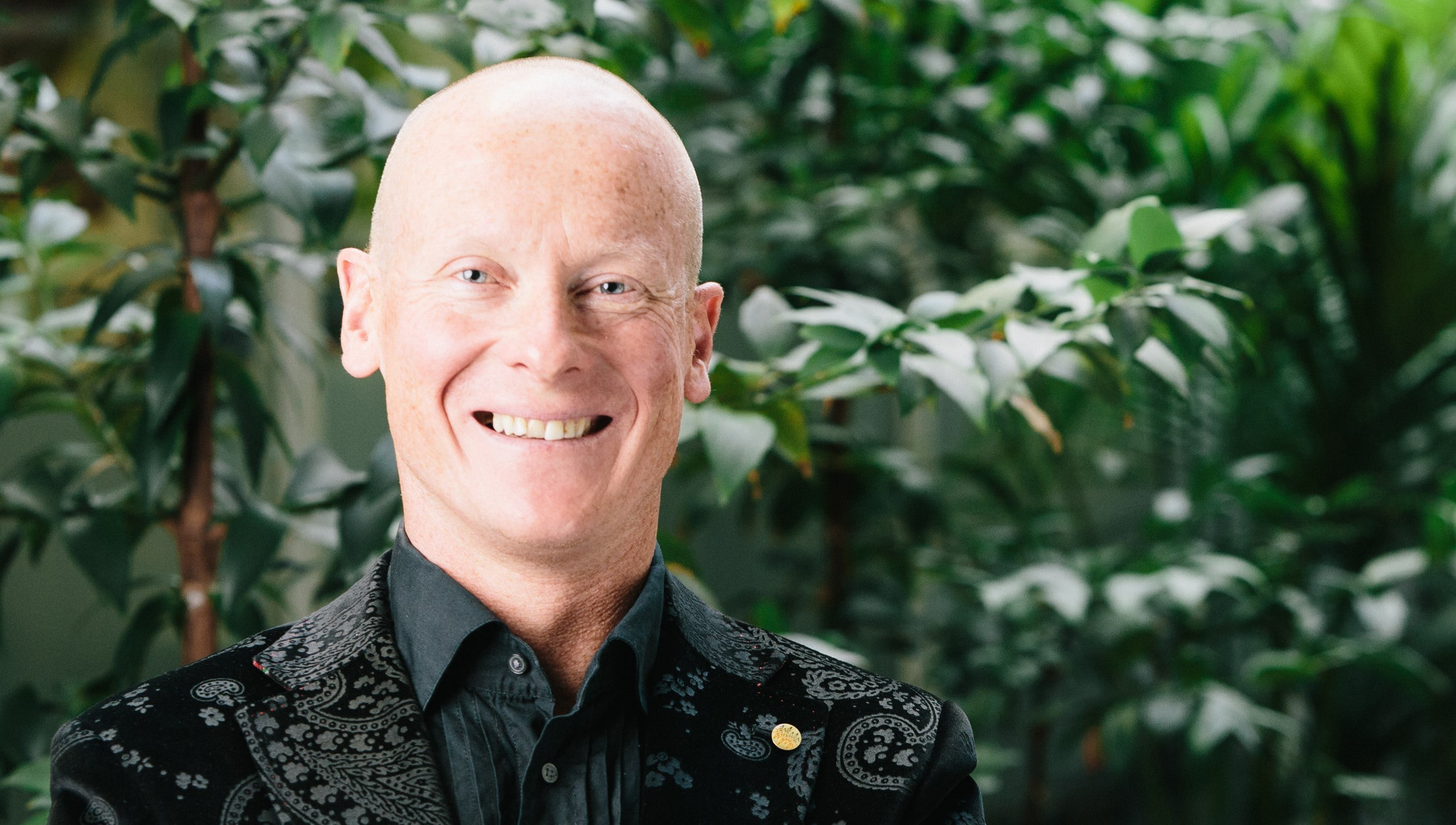 Jon is seen smiling broadly and wearing a black paisley business jacket and shirt. He is standing in front of some tall green plants