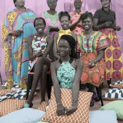 A group of South Sudanese women are positioned in a triangluar formation. They are wearing bright coloured clothing and holding cushions.